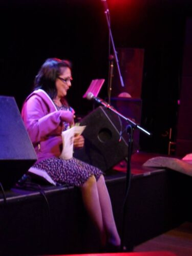 Kuli Kohli sat on the edge of a stage giving a reading into a microphone.