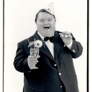 Promotional black and white photograph of Lung Ha theatre's, The Never Ending Conga, featuring actor Robin Lamb in a suit and party hat. He has a cocktail in one hand.