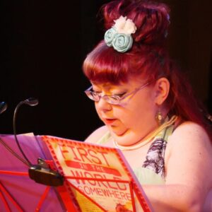 Photo of disabled performer Penny Pepper reading from her memoir propped on a music stand