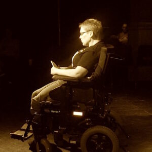 photo of PhD student and writer Lisa Davies on stage reading a poem