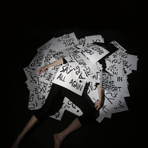 A person lies under a pile of cards with various phrases on
