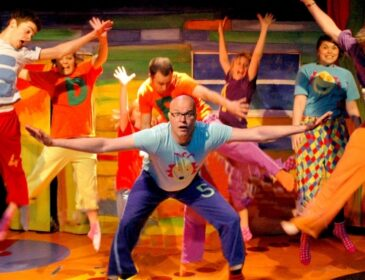 A group of adults in pyjamas jump around against a brightly coloured set