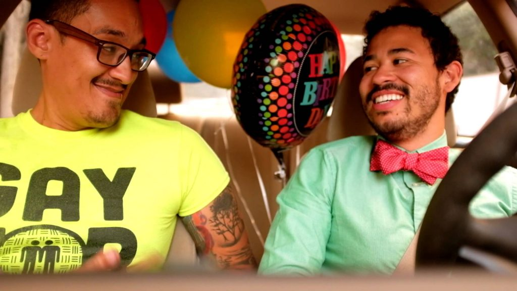 photo of two gay men in the front seat of a car smiling at each other