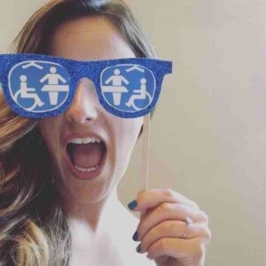 Selfie of Gemma Nash, holding a pair of blue glasses with accessible toilet symbols on in front of her eyes