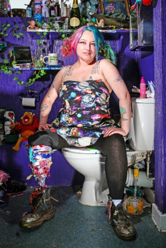 photo of performer and writer Jackie Hagan sitting in a bathroom