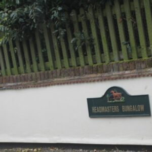 A white wall beneath a wooden fence bears the plaque 'Headmasters Bungalow'