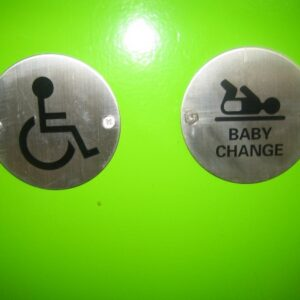 A door with a greenish hue holds two signs. The wheelchair user defining accessible toilet and the other a baby being changed over the words changing room