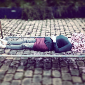 A photograph of a woman lying on a bed on a cobbled street. She has flowers over her face.