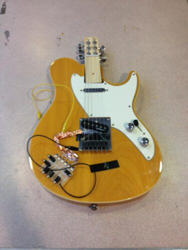 Photograph of a specially modified guitar with a wires connected to it and a short neck.