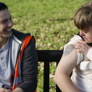 image of a young woman and man sitting on a park bench