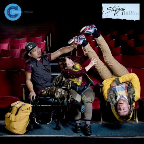 Photograph of three dancers in theatre stalls, one is upside down in his seat, another a wheelchair user