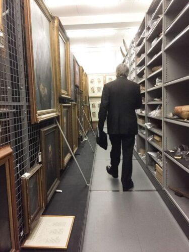 Photo of film-maker David Hevey in a suit walking amongst the shelves within a museum archive