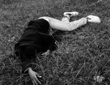 A black and white photograph of a person lying, fully clothed on a grassy floor.