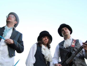 photo of 3 members of the band wearing frilly shirts and hats