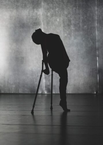 Promotional photgraph of Candoco Dance Company's Beheld featuring a silhoutted female dancer using crutches standing on her tip toes and arching her head backwards.