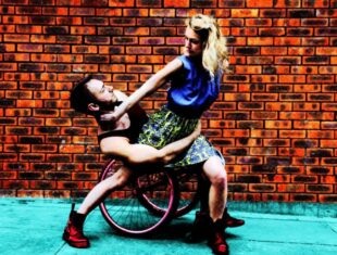 photo of two dancers against a brick wall background