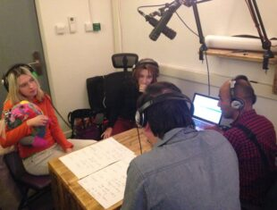 Photograph of four people in a radio studio sitting around a table and discussing things.
