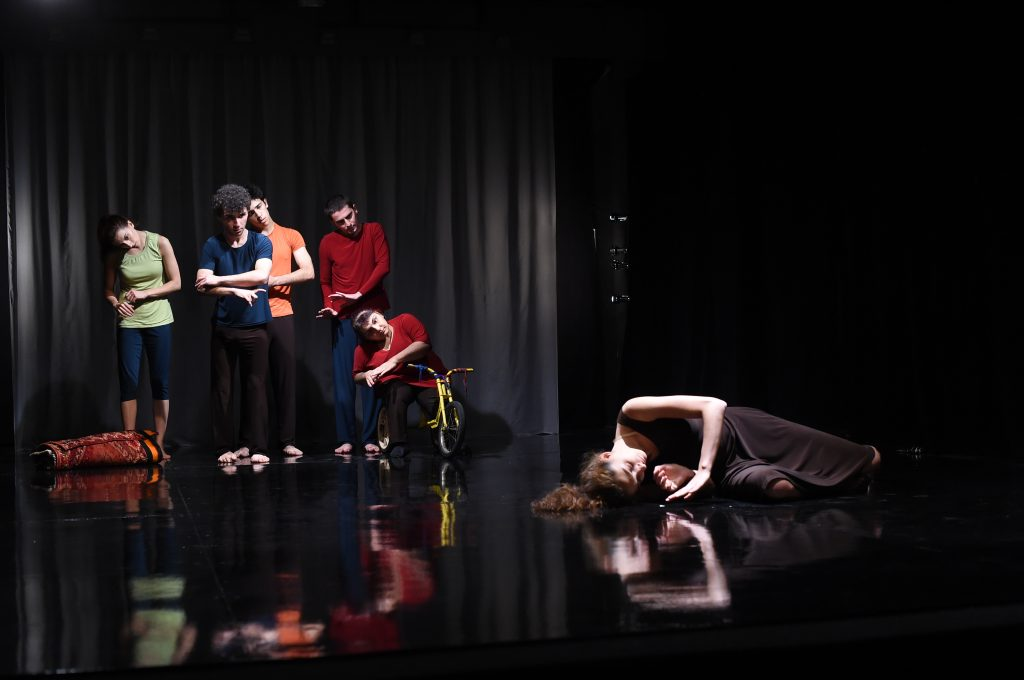 Photograph of a performance of NCA Small Theatre's Hiraeth, a woman lies on a reflective stage, five more performers stand behind her, their heads cocked to one side.