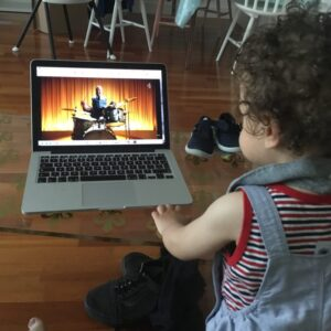 toddler watching the superhumans ad on a laptop
