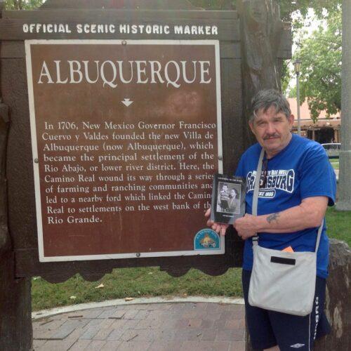 photo of author Peter Street outside a plaque detailing the establishment of Albuquerque