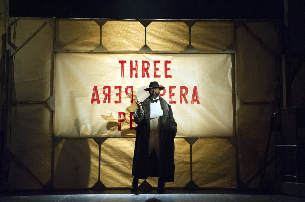 The Balladeer poses in front of a banner reading THREE Opera