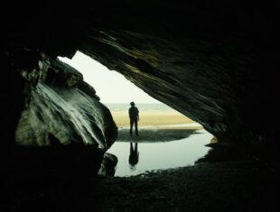 FIlm still from Notes on Blindness depicting the protagonist standing silhouetted outside a cave