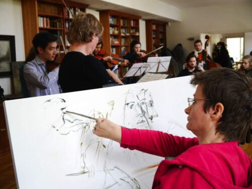 Tanya Raabe-Webber at the easel engaged in a live portrait session
