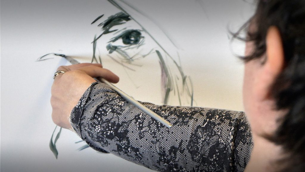 photo taken across the arm of the artist in the act of drawing a portrait of a woman