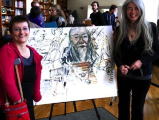 photo of the artist and the musician standing on either side of the portrait on an easel
