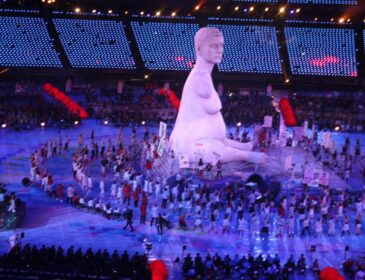 Photograph of the 2012 Paralympic Opening Ceremony showing a crowd of disabled performers holding signs and gathered around a giant replica of Marc Quinn's sculpture Alison Lapper Pregnant