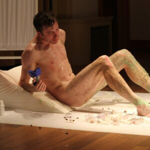 Photo of young naked man lying on a bed covered with green glitter