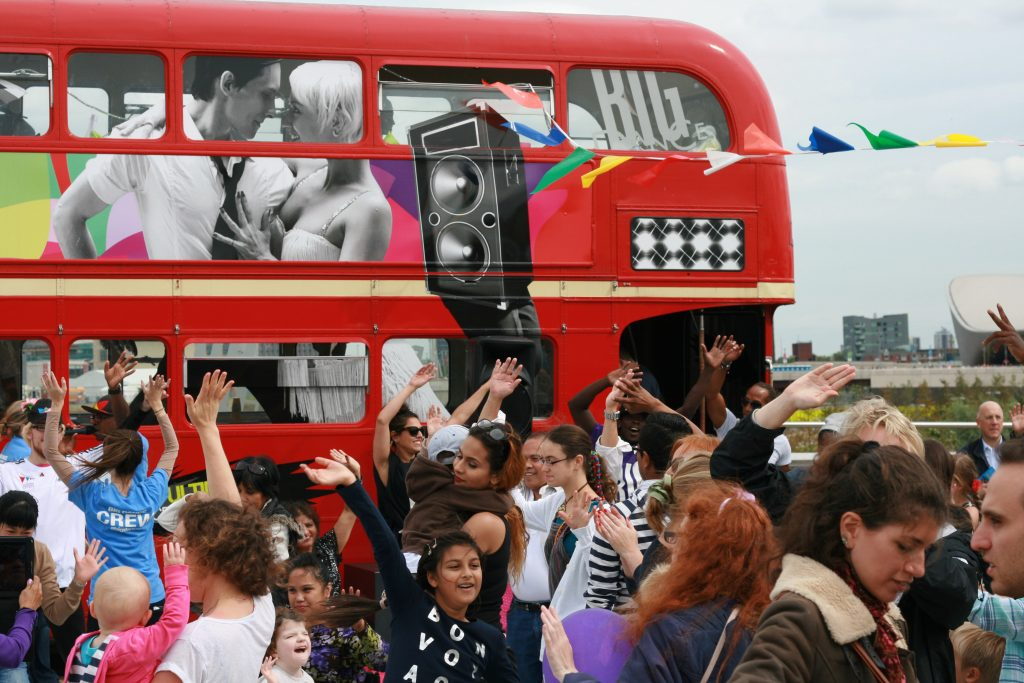 A photograph of a group of people dancing around outside a red London bus