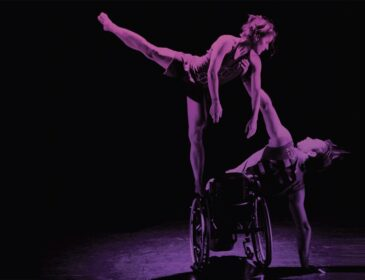 photo of two dancers in purple against a black background