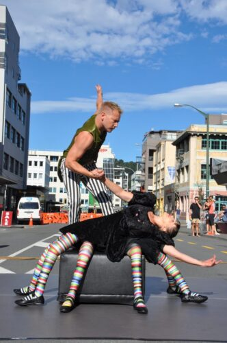 Two performers holding hands, one is standing vertical the other laid out horizontal with 8 legs.