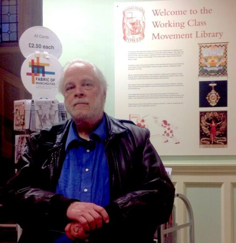 """photo of elderly man next to a poster saying """"welcome to the working class movement library'"""