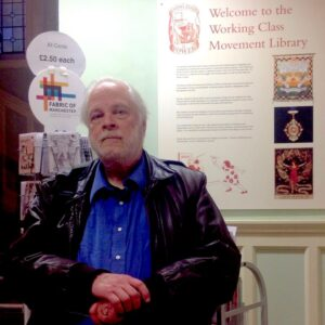 photo of Professor Fred Whitehead standing in front of a poster saying 'Welcome to the working class movement library.