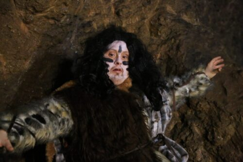 Photograph of Danny Smith dressed as a caveman with facepaint Aon and big black hair