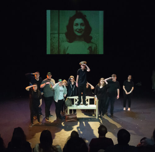 photo of a group of young performers on stage. The face of a woman is projected onto a screen behind the performers