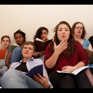 Nine people sit or lie on a mattress in a small room, crowded closely together, looking into the camera. They all read from books. One of them is using British Sign Language. Left to right: Robert Softley Gale, Nathan Gale, Lake Montgomery, Sandra Alland, Izdihar Alodhami, Bea Webster, Cate Lauder, Matson Lawrence, Chris Red. Photo by Ania Urbanowska (still from filming).
