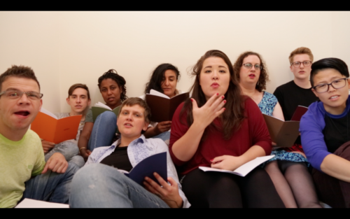 Nine people sit or lie on a mattress in a small room, crowded closely together, looking into the camera. They all read from books. One of them is using British Sign Language.