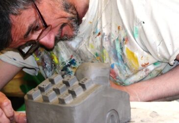 Artist Cameron Morgan in a stained t-shirt works on a ceramic cast of a telephone