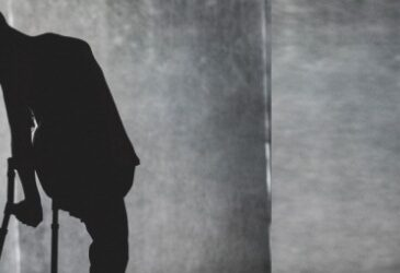 Photograph of a silhoutted dancer on crutches