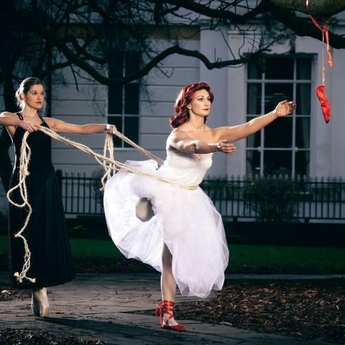 Cinematic style photograph by Sean Goldthorpe of two female dancers. One has a rope around the other one's waist, they are in dancing costumes.