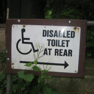 colour photograph of a white sign bearing a black wheelchair user sign, the words disabled toilet at rear and an arrow pointing right