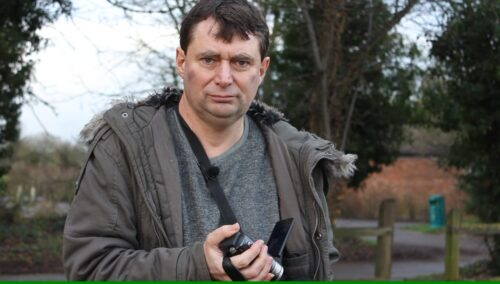 Film still depicting a man with a camcorder looking straight at the camera in a rural setting