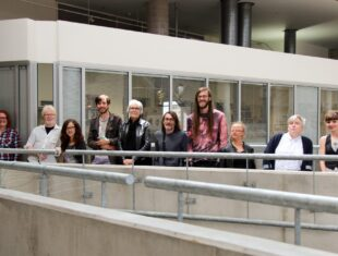 A photograph of a group of artists standing in front of a white building, smiling