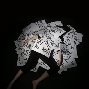 Photograph of Nye Russel-Thompson lying under a pile of prompt cards