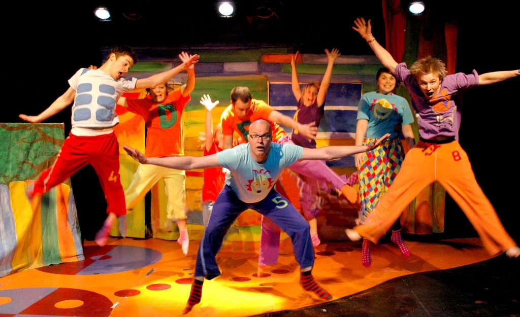 photo of a group of brightly dressed actors posing on a bright yellow and red stage
