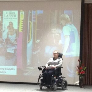 LIsa Davies on stage in her wheelchair with a screen behind her projecting a collage of images of dasabled people
