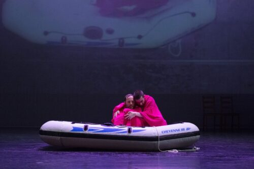 Ian Johnston and Gary Gardner sit in a dinghy embracing as they are wrapped in pink towels.